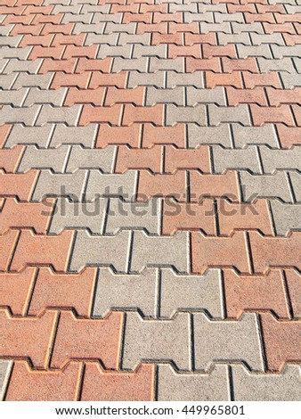 Decorative colorful sidewalk pavement. Tiled floor with grey tiles crossed by a diagonal double stripe of red tiles viewed at a low angle, full frame background pattern - stock photo