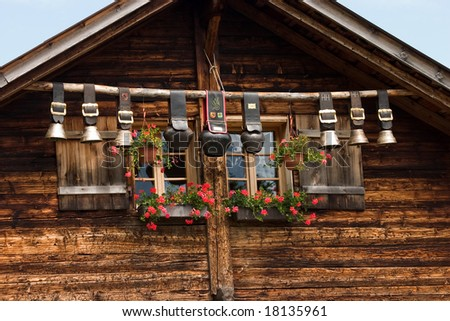 Decorative cow bells under the roof of an alpine mountain hut, Switzerland - stock photo