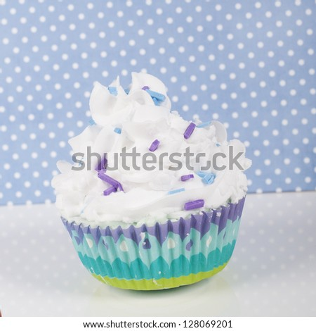Decorative cupcake on baby blue dotted background