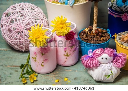 Decorative decoupage jars, handmade dolls and flowers on table on bright wooden background
