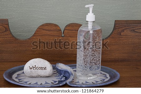 Decorative Display of Hand Sanitizer on antique carved hall table with Welcome sign on blue design plate. Grass Cloth wall decor