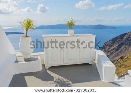 Decorative elements adorn input group in the traditional Greek house and rocks of the Therasia on backdrop.Santorini island.Cyclades.Greece.Europe.