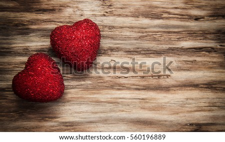 Decorative fabric hearts on a wooden background