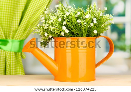 Decorative flowers in watering can on windowsill - stock photo