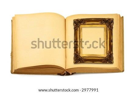 decorative frame lying on an open book isolated on white - stock photo
