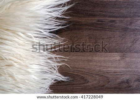 Decorative fur carpet on wood floor background - stock photo