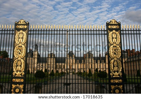 Decorative gate with golden ornaments - entrance to Fontainebleau castle in France. Chateau is inscribed to UNESCO world heritage list. - stock photo