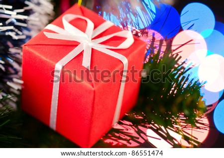 decorative gift box on christmas tree with blurred lights on background. Shallow DoF - stock photo