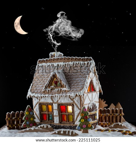 Decorative gingerbread house with lights inside and smoke coming out the chimney on black background with moon and stars . Rural Christmas night scene - stock photo