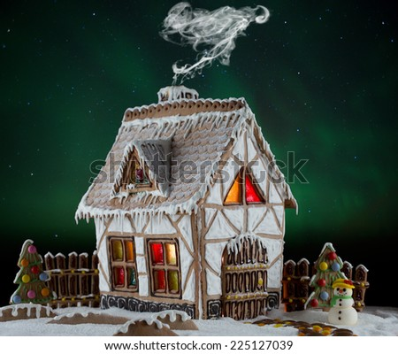 Decorative gingerbread house with lights inside and smoke coming out the chimney on Northern lights background with moon and stars . Rural Christmas night scene - stock photo