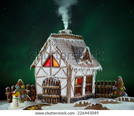 Decorative gingerbread house with lights inside and smoke coming out the chimney with Northern lights on background. Rural Christmas night scene - stock photo