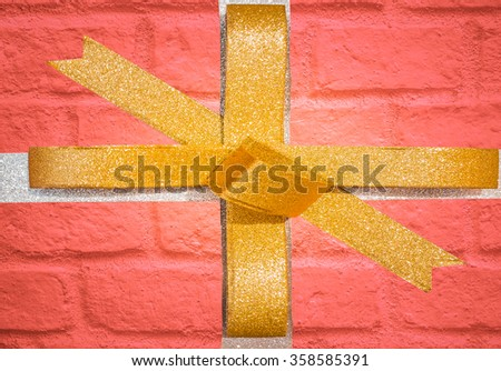 Decorative golden ribbon and bow on a background of red brick wall with copyspace. - stock photo
