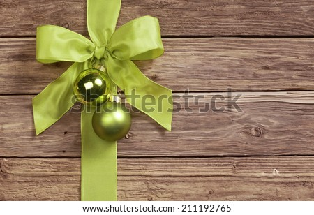 Decorative green bow decorated with two Christmas bauble ornaments on a wooden background with copyspace for your seasonal greeting - stock photo