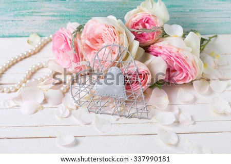 Decorative  grey heart and sweet pink roses on white background against turquoise wall. Selective focus.
