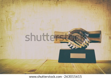 decorative handshake gadget over wooden table. business concept. image is retro filtered - stock photo