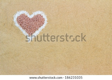 Decorative heart shape formed of sand symbolic of love and romance with copyspace for your Valentines Day, wedding or anniversary message - stock photo