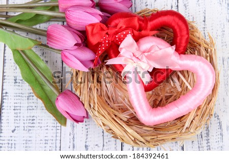 Decorative hearts in nest, on color wooden background - stock photo