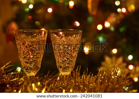 Decorative holiday background with champagne glasses on a background of a Christmas tree with toys and lights