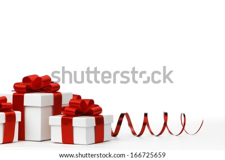 Decorative holiday gifts in white boxes with red ribbons on white background - stock photo