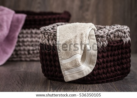 Decorative knitted baskets with ribbons on wooden background
