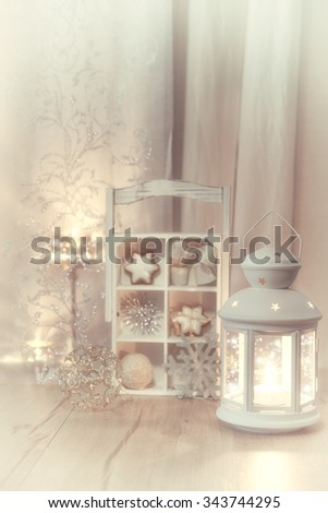 Decorative lantern, candles and Christmas decorations, shallow DOF; focus on the lantern top, space for your text - stock photo