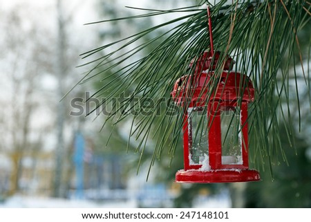 Decorative lantern hanging on fir tree branch on winter scene background - stock photo