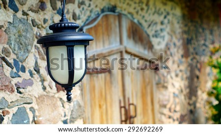 Decorative lantern hanging on the wall of old house
