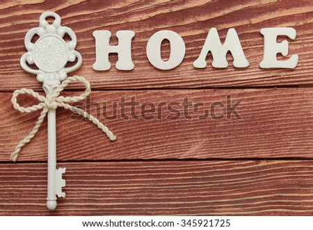 Decorative letters forming word HOME and a  key tied with a bow on wooden background    - stock photo