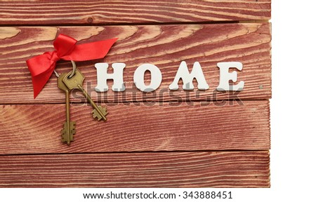 Decorative letters forming word HOME with bunch of keys on wooden background - stock photo
