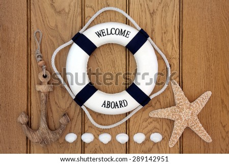 Decorative lifebuoy, wooden anchor, starfish and cockle shells over old oak background. - stock photo