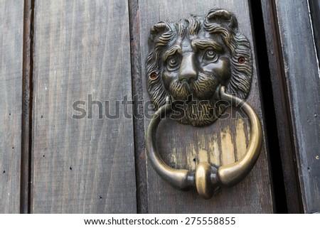 Decorative lion head door knob on a vintage wooden door - stock photo
