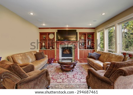 Decorative living room with leather sofas, hardwood floor, and a rug. - stock photo