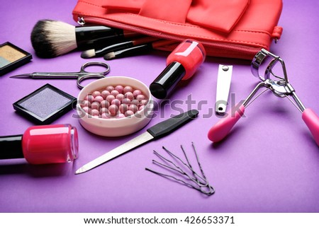 Decorative makeup cosmetics and manicure tools on purple background