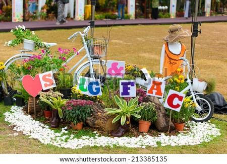 Decorative mannequin and bicycle in a flower garden at FLORIA event held in Putrajaya, Malaysia. - stock photo