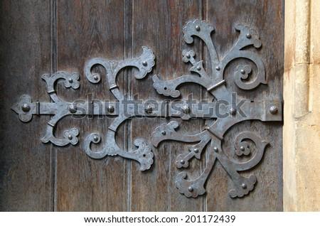 Decorative metal hinge on an old wooden door - stock photo