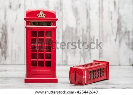 Decorative money box as classic British red phone booth on white wooden background - stock photo