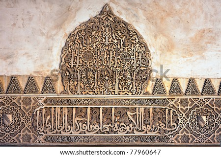 Decorative motifs and arabic inscription on the wall of Alhambra, Palace of the Nazaries, in Granada, Spain. - stock photo