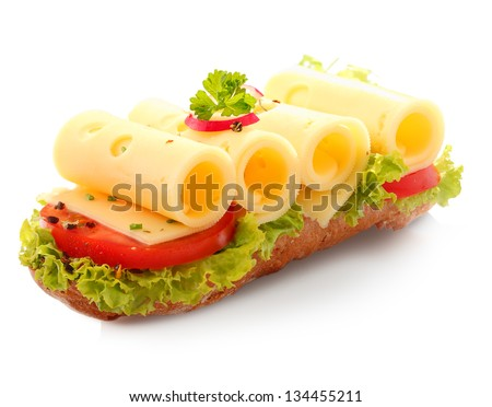 Decorative open baguette sandwich with four slices of rolled cheese on top of fresh lettuce and sliced red tomato on a white background - stock photo