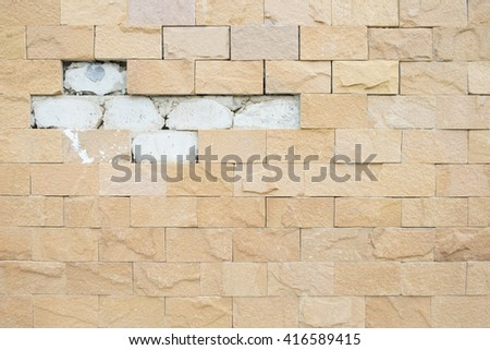 Decorative orange stone tiles, old stone Cladding, Wall damaged by time,The refinement of the construction, background texture - stock photo