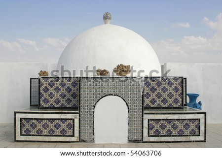 Decorative oriental, arab style cupola on top of the building in Tunisia with desert roses and vases on it
