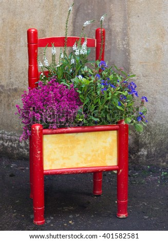Decorative painted chair planted with various flowers as an eyecatcher for the home or garden. - stock photo