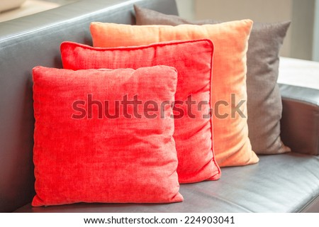 Decorative pillows on black leather sofa  - stock photo