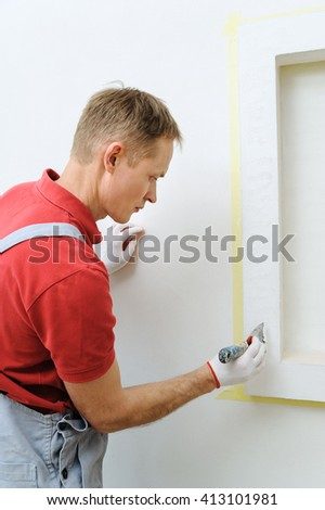 Decorative plaster coating. Man does ragged texture on the wall using a spatula.
