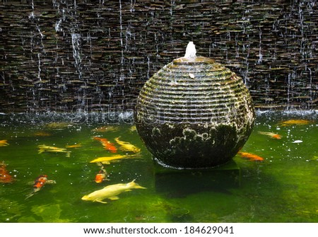 Decorative pond with fountain and gold fish. - stock photo