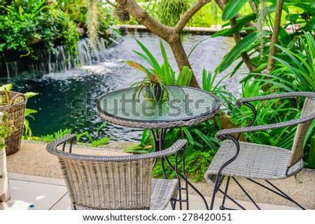 Decorative pond with ornamental plants  and green garden - stock photo