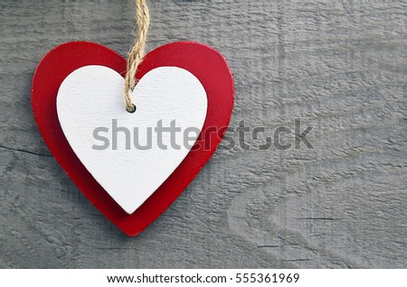 decorative red and white wooden hearts on a grey wooden backgroundtwo valentine hearts