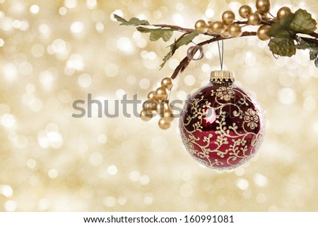 Decorative Red Christmas Ornament hanging from a branch in front of a glittering gold background.