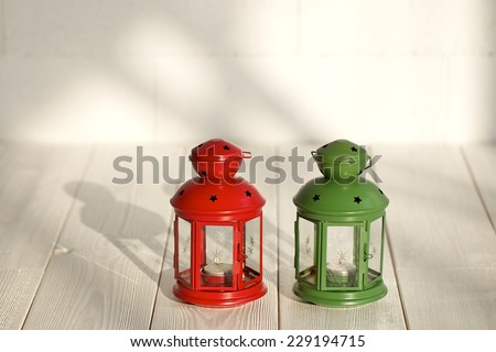 Decorative red metal lantern with a star cutout and small window lit by a glowing candle with copyspace for Christmas. White wood floor and wall. - stock photo