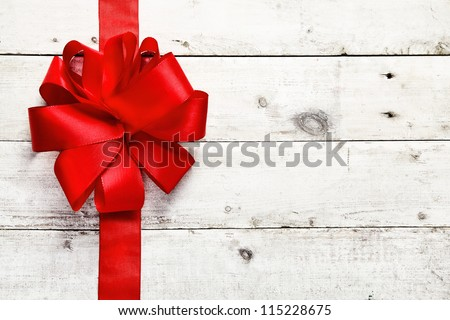 Decorative red ribbon and bow on a background of white painted rustic boards with copyspace - stock photo