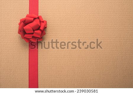 Decorative red ribbon and bow over corrugated cardboard    - stock photo
